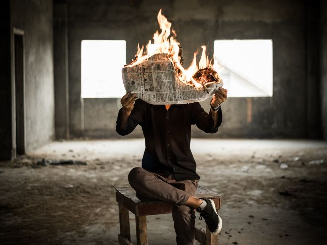 Man sitting on a chair reading a burning newspaper